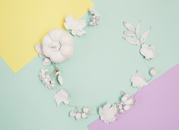 Frame mockup with pumpkin, berries and leaves on turquoise Premium Photo