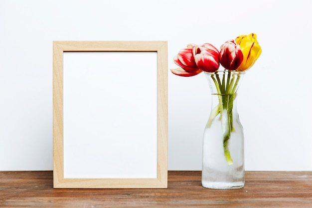 Frame near vase with flowers Free Photo