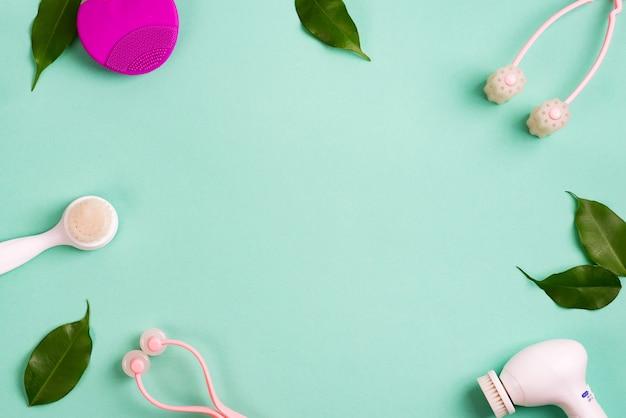 Рамка аксессуаров для ухода за лицом и зелеными листьями. чистую кожу другой кистью на зеленом Premium Фотографии