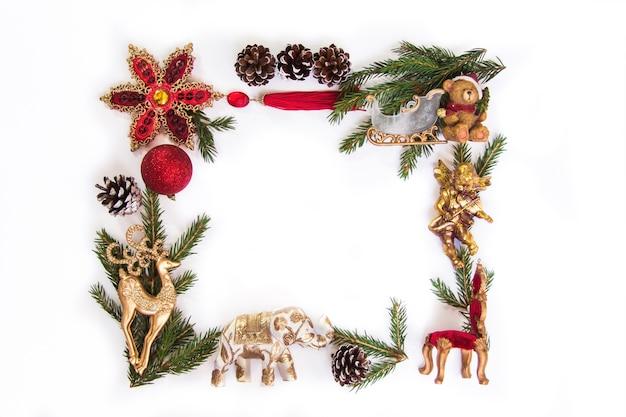 クリスマスツリーのフレームは、白い背景の上の赤と金の装飾を分岐しますフラットレイコピースペース Premium写真