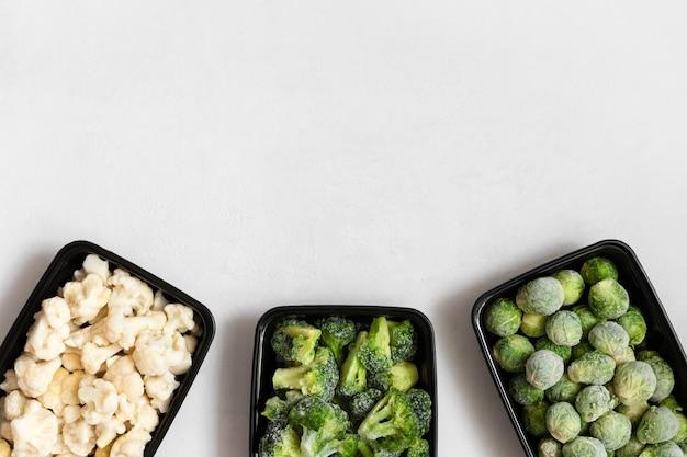 Рамка из замороженных овощей в пластиковых контейнерах на белом фоне. набор разных кочанов. место для текста. вид сверху, плоская планировка. Premium Фотографии