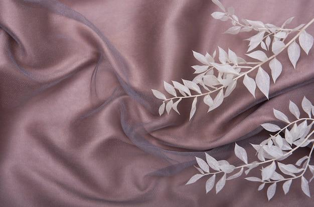 薄茶色の壁に葉を持つ白い枝のフレーム Premium写真