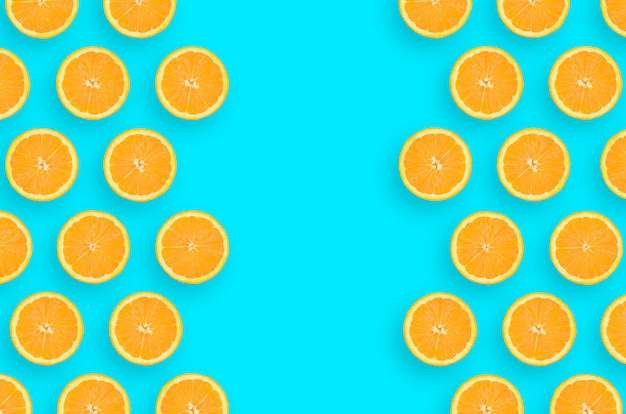 Frame of an orange citrus slices on bright blue background Premium Photo