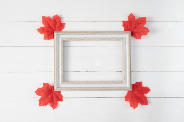 Frame and red maple leaves on white wooden background. autumn, fall , top view, copy space. Premium Photo