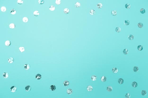 Frame of shiny silver confetti on pastel turquoise background Premium Photo