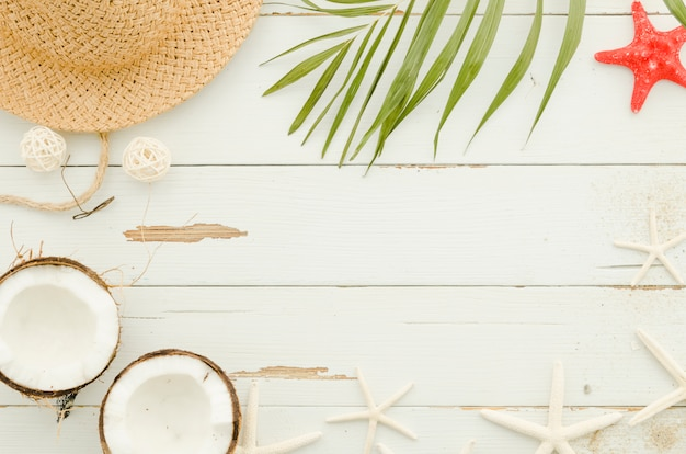 Frame of straw hat, sea stars and palm leaf Free Photo
