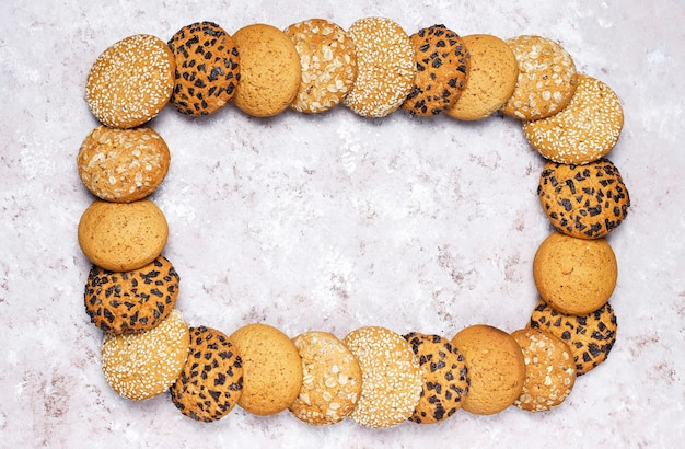 Frame of various american style cookies on a light concrete background. shortbread with confetti, sesame seed, peanut butter, oatmeal and chocolate chip cookies. Free Photo