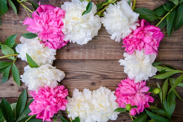 Frame of white and pink peonies on wooden background Premium Photo