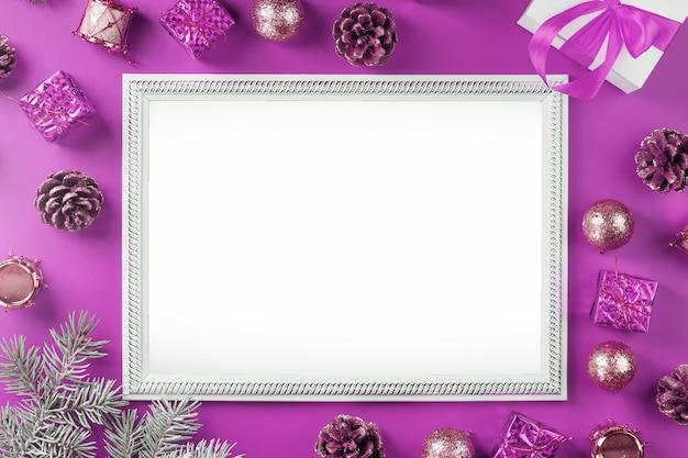 ピンクの背景にクリスマスの装飾やギフトと空の空白のフレーム。はがきメリークリスマスと新年あけましておめでとうございます。あいさつ文用の空きスペースがあります。 Premium写真