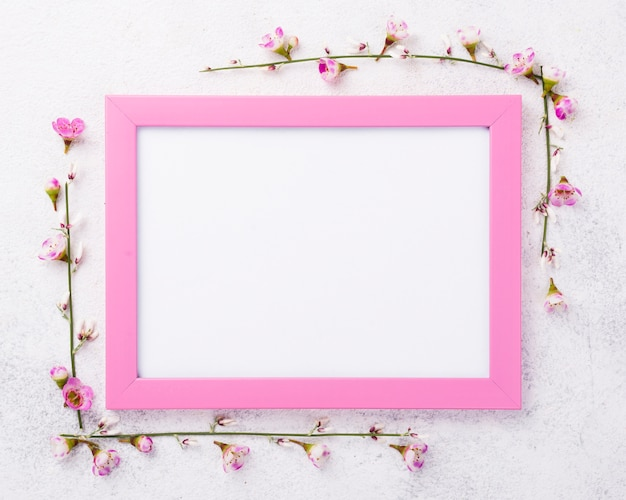 Frame with flowers beside Free Photo