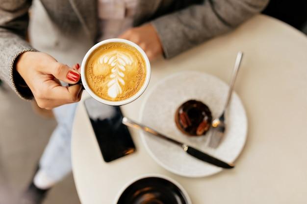 Sopra il telaio della giovane donna tiene una tazza di caffè sulla caffetteria esterna con dessert Foto Gratuite