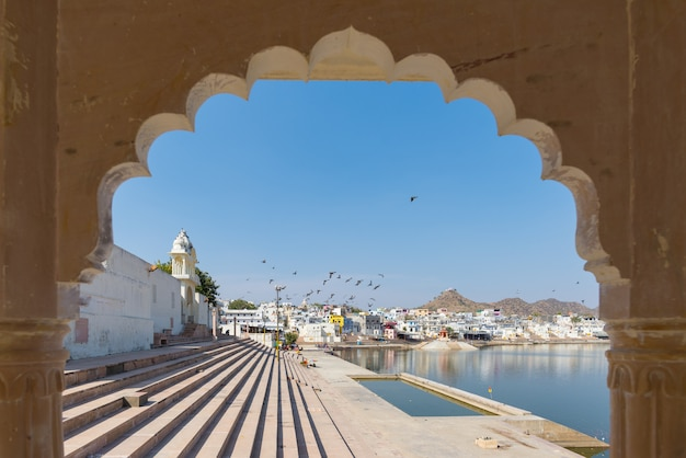 Framed view from archway at pushkar, rajasthan, india. temples, buildings and ghats on the holy water of the lake at sunset. Premium Photo