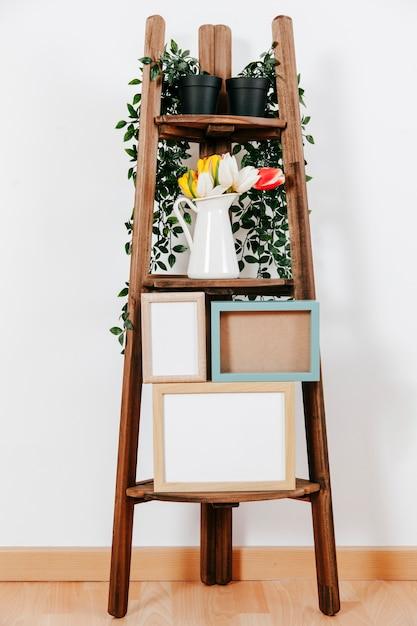 Frames and flowers on shelf Free Photo