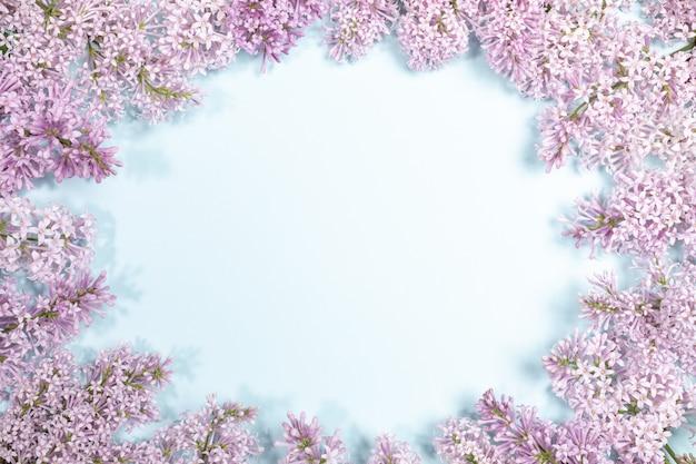 Обрамление сиреневые цветы светло синий фон с копией пространства. Premium Фотографии