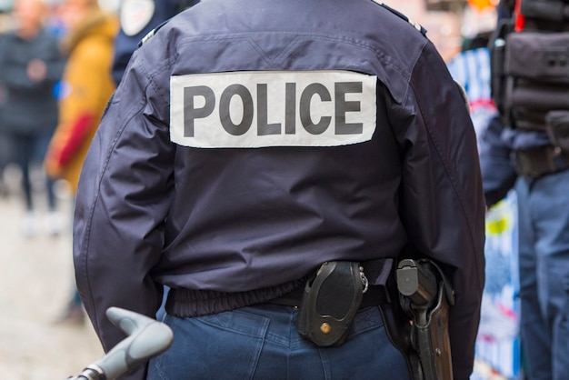 France, back of  police officer in paris Premium Photo