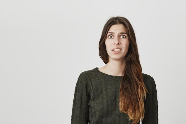 La giovane donna impazzita si fa rabbrividire da qualcosa di disgustoso o strano, infastidito dalle smorfie Foto Gratuite