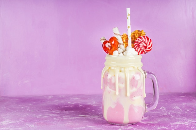Freakshake from pink smoothie, cream. monstershake with lollipops, waffles and marshmallow. Premium Photo
