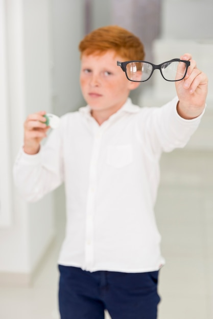 Freckle boy holding eyeglasses and contact lenses container Free Photo
