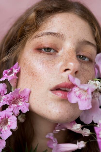 ピンクの花を持っているそばかすのある女性 無料写真