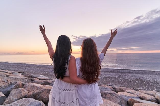 Свободная беззаботная счастливая дочь и мама в белых платьях стоят вместе на камнях с распростертыми объятиями на берегу моря на закате летом Premium Фотографии