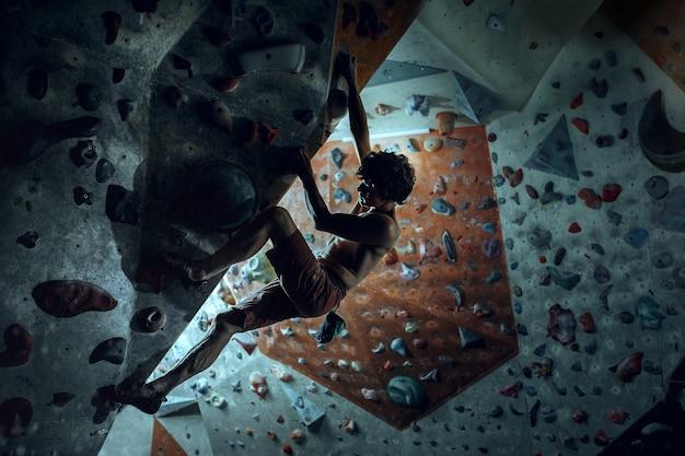 Free climber climbing artificial boulder indoors Free Photo