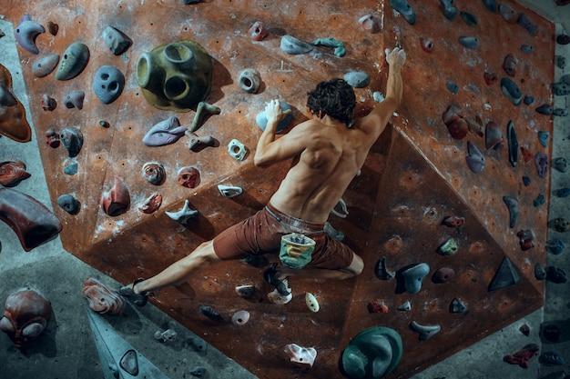 Свободный альпинист молодой человек, восхождение на искусственный валун в помещении. Бесплатные Фотографии