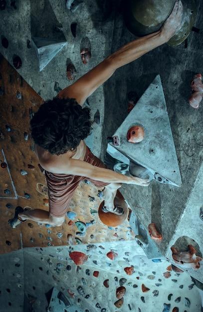 Free climber young man climbing artificial boulder indoors Free Photo