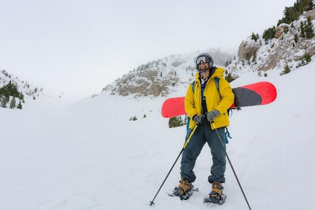 Фрирайдер со снегоступами и сноубордом на спине. Premium Фотографии