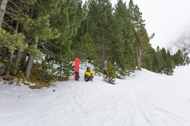 Free rider with snowshoes and snowboard on his back. Premium Photo