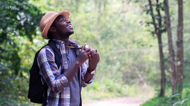 Freedom african man traveler с рюкзаком стоит и держит пленочную камеру Premium Фотографии
