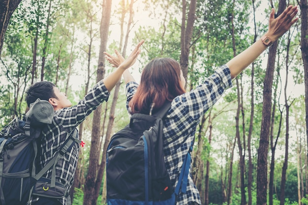 Freedom couples hiker with backpack open arms enjoy the nature in a big forest. Premium Photo