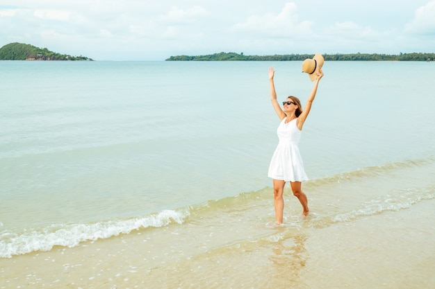 Freedom happy woman with raised arms on the beach at sunny day Premium Photo