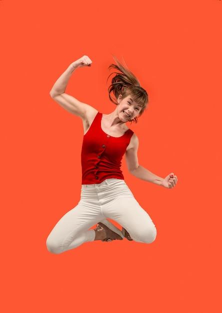 移動の自由。オレンジに対してジャンプして身振りで示すかなり幸せな若い女性の空中ショット 無料写真