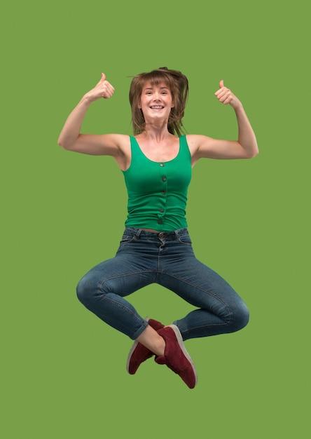 移動の自由。緑の上でジャンプして身振りで示すかなり幸せな若い女性の空中ショット 無料写真