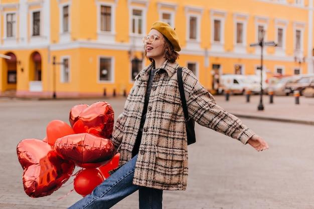 청바지와 노란색 베레모의 자유를 사랑하는 여성은 도시 주변 산책을 즐깁니다. 무료 사진