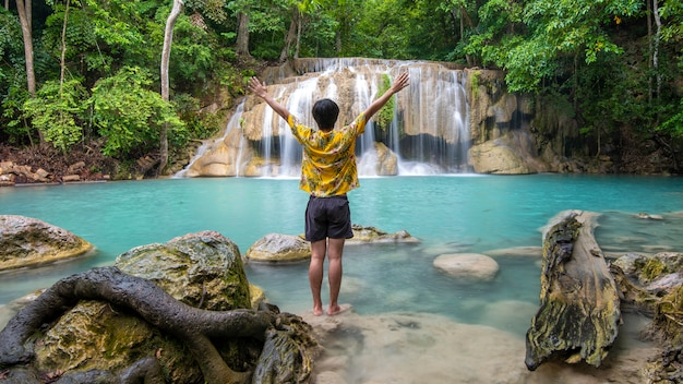 A freedom man is enjoying with beautiful waterfall in tropical forest Premium Photo