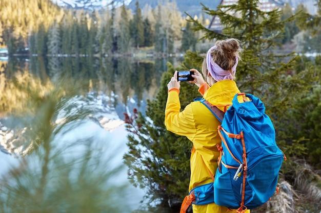 自由旅行者は、風光明媚な自然の景色の写真を撮り、山と森のある美しい湖をキャプチャしようとし、後ろに立ちます 無料写真
