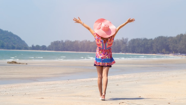 Freedom woman standing arms outstretched back and enjoy life on the beach Premium Photo