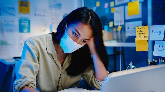 Азиатские женщины-фрилансеры носят маску для лица, усердно работая с ноутбуком в новом обычном офисе. перегрузка дома по ночам, самоизоляция, социальное дистанцирование, карантин для профилактики коронавируса. Бесплатные Фотографии