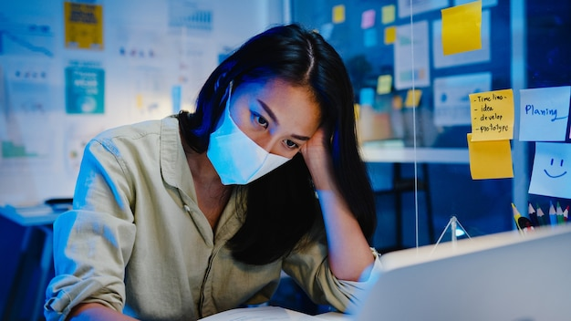 Freelance asia women wear face mask using laptop hard work at new normal office. working from home overload at night, self isolation, social distancing, quarantine for corona virus prevention. Free Photo