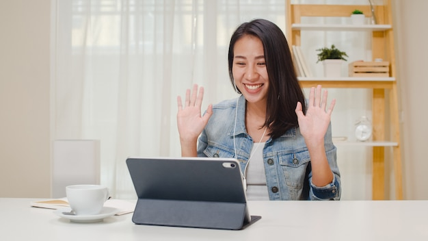Freelance business women casual wear using tablet working call video conference with customer in workplace in living room at home. happy young asian girl relax sitting on desk do job in internet. Free Photo