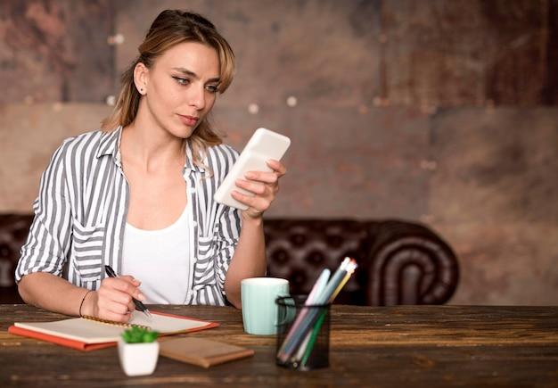 モバイルを確認するフリーランスの女性 無料写真