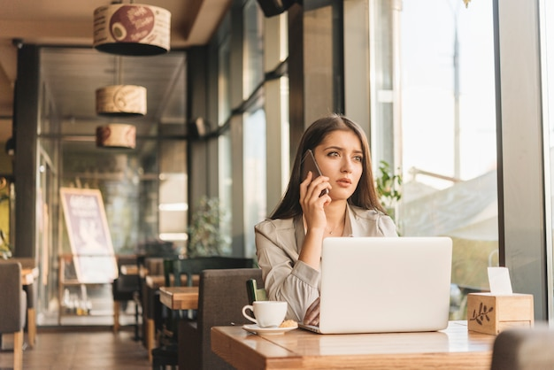 Freelance woman working with laptop in coffee shop Free Photo