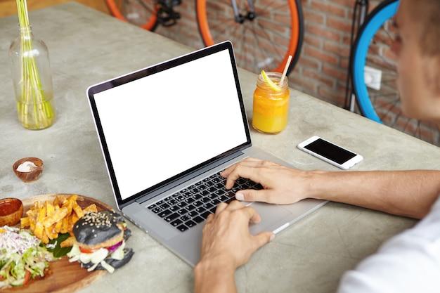 햄버거와 함께 카페 테이블에 앉아 점심 시간 동안 랩톱 컴퓨터를 사용하여 원격으로 작업하는 흰색 티셔츠의 프리랜서 무료 사진