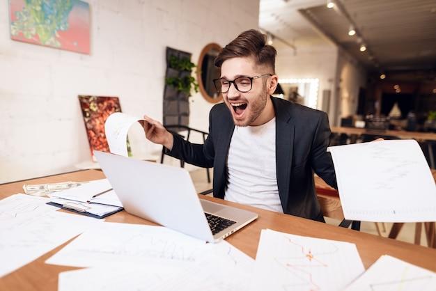 Freelancer man looking happy at laptop sitting at desk. Premium Photo