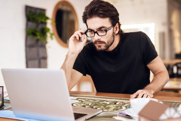 Freelancer sitting at desk works at project. Premium Photo
