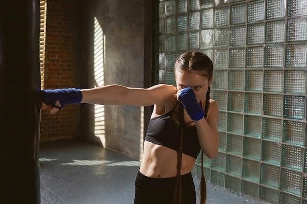 Congelare il ritratto di azione di incredibile combattente femminile giovane concentrato con corpo muscoloso perfetto che si esercita da solo in palestra Foto Gratuite