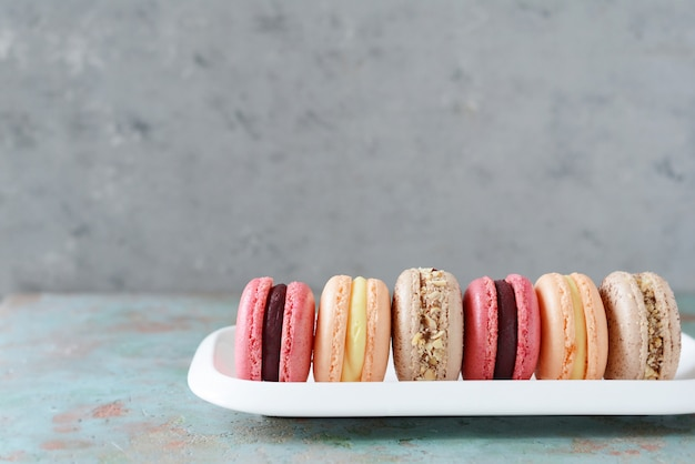 French assorted macarons cakes on a rectangular dish. colorful small french cakes. top view. Premium Photo