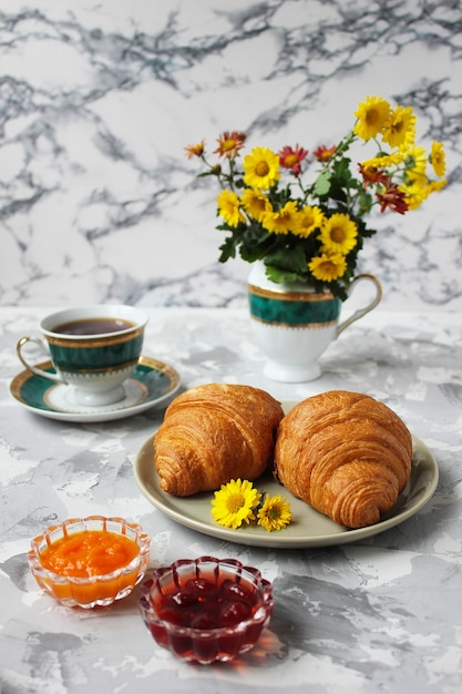 French breakfast with croissants, apricot jam, cherry jam and a cup of tea, red and yellow flowers Free Photo
