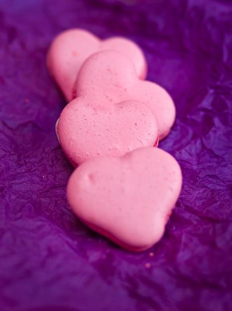 Французские разноцветные макаруны с сердечками на фиолетовом фоне Premium Фотографии